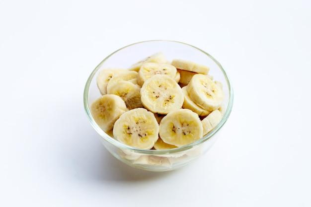 Plasterki banana w szklanej misce na białym tle.