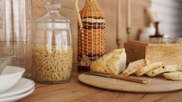 Plasterki białego chleba na drewnianej tacy. nowoczesna kuchnia w stylu skandynawskim. makaron w szklanym słoiku
