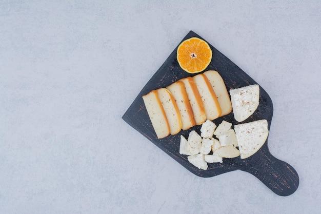 Plasterki białego chleba z plasterkiem pomarańczy na desce do krojenia. zdjęcie wysokiej jakości