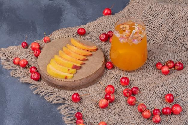 Plasterki brzoskwini, wiśnie i szklankę soku owocowego na niebiesko.