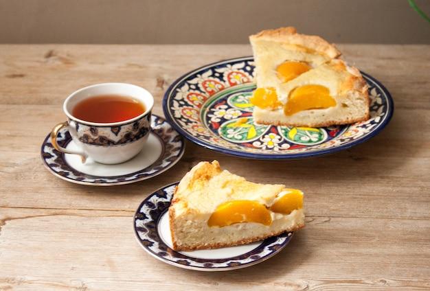 Plasterki brzoskwiniowe ciasto morelowe na jasnym spodku z filiżanką herbaty na drewnianym stole