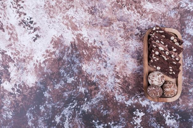 Plasterki ciasta kakaowego i pierniki na drewnianym talerzu.