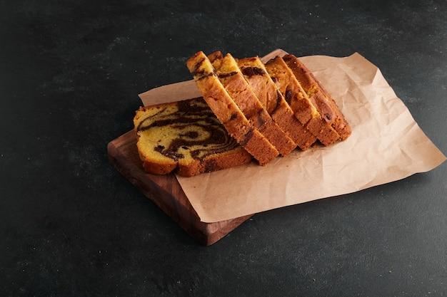 Plasterki ciasta kakaowego na drewnianej desce.