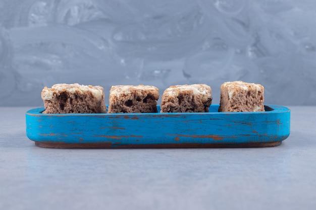 Plasterki ciasta na drewnianym talerzu na marmurze