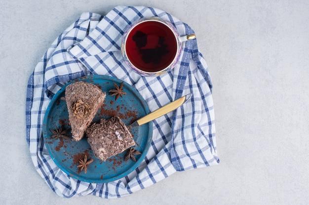 Plasterki ciasta na talerzu obok filiżanki herbaty na marmurowym stole.