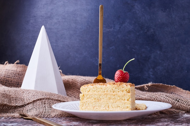 Plasterki ciasta z truskawkami na białym talerzu.
