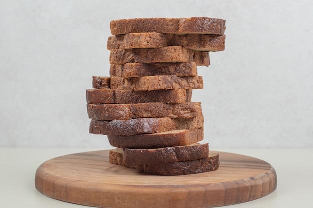 Plasterki ciemnego chleba na białym tle. wysokiej jakości zdjęcie