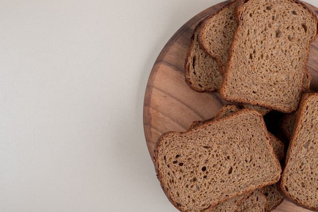 Plasterki ciemnego chleba na drewnianym talerzu. wysokiej jakości zdjęcie