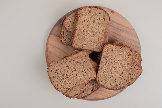 Plasterki ciemnego chleba na drewnianym talerzu