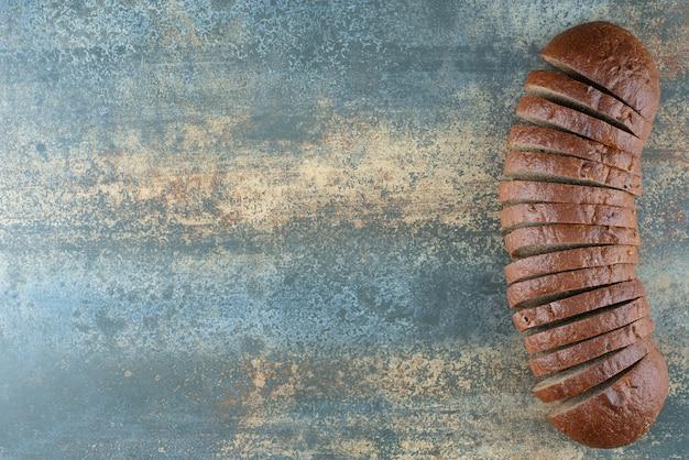 Plasterki ciemnego chleba na tle marmuru