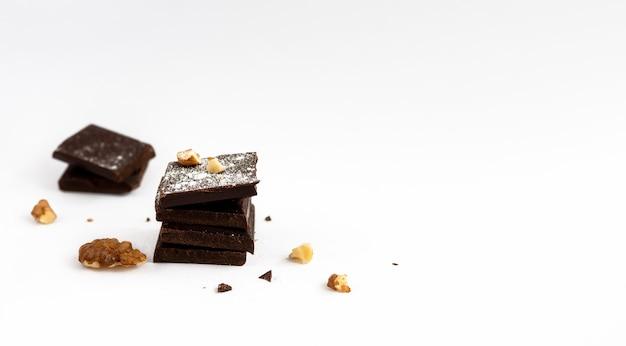 Plasterki ciemnej czekolady posypane orzechami włoskimi i cukrem pudrem na białym tle na białej powierzchni, zbliżenie