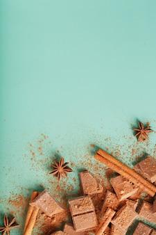 Plasterki ciemnej czekolady z cynamonem i przyprawami na pastelowo zielonej powierzchni