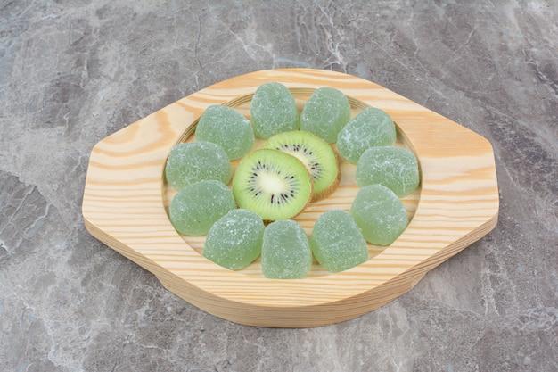 Plasterki cukierki kiwi i marmolady na drewnianym talerzu.