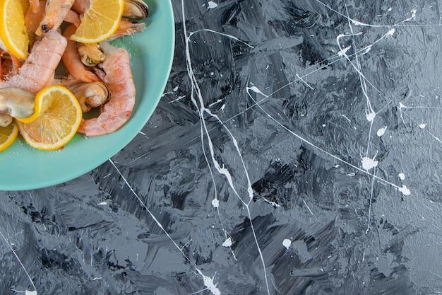 Plasterki cytryny i krewetki na talerzu, na marmurowym tle.