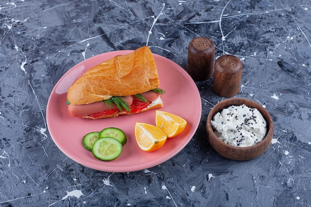 Plasterki cytryny i ogórka, kanapka na talerzu obok miski sera, na niebiesko.
