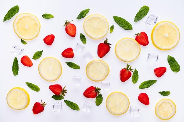 Plasterki cytryny, liście mięty, truskawka i kompozycja kostek lodu