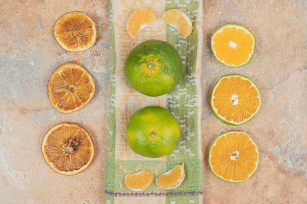 Plasterki cytryny, mandarynki i pomarańczy na marmurowej powierzchni.