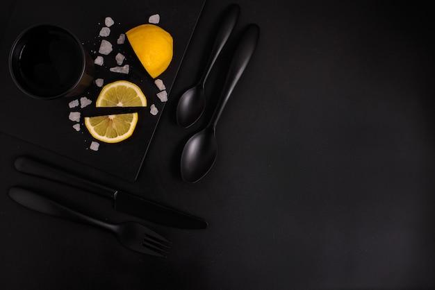 Plasterki cytryny na czarnym tle z czarne sztućce, czarne szkło i czarny talerz, widok z góry