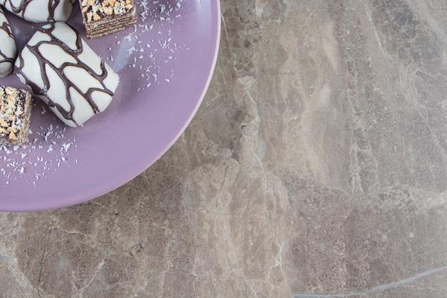Plasterki czekolady z orzechami na drewnianym talerzu na marmurze.