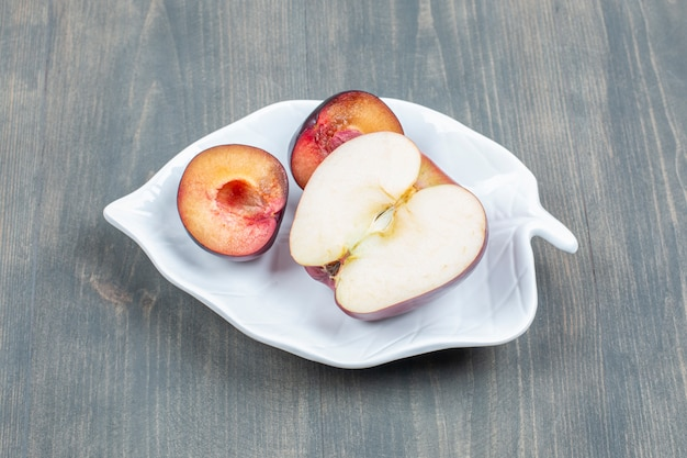 Plasterki czerwone jabłko z pokrojoną śliwką na białym talerzu