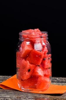 Plasterki czerwonego arbuza w szklanym słoju podczas śniadania, pyszny i soczysty arbuz na stole w puszkach