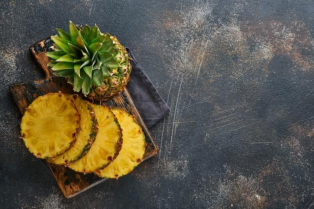 Plasterki dojrzałego ananasa na ciemnym brązowym tle kamienia. owoce tropikalne. widok z góry. wolne miejsce na tekst. makieta.