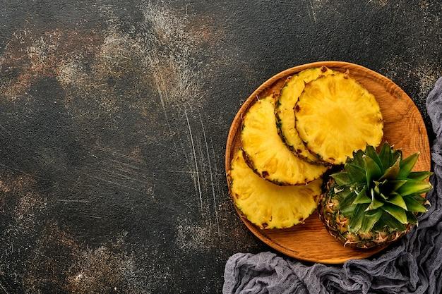 Plasterki dojrzałego ananasa na ciemnym brązowym tle kamienia. owoce tropikalne. widok z góry. wolne miejsce na tekst.