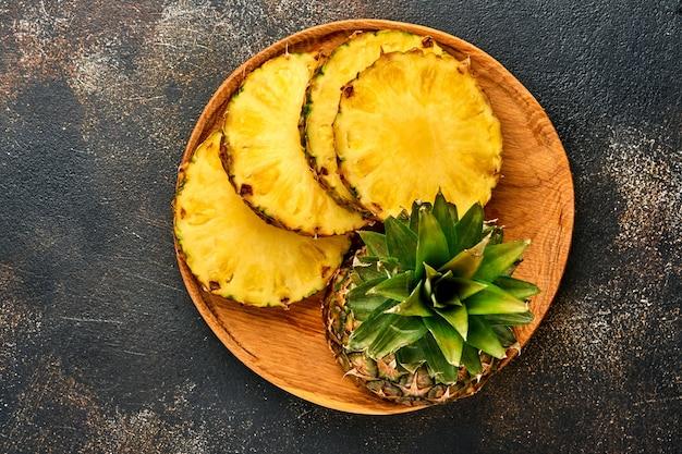Plasterki dojrzałego ananasa na ciemnym brązowym tle kamienia. owoce tropikalne.