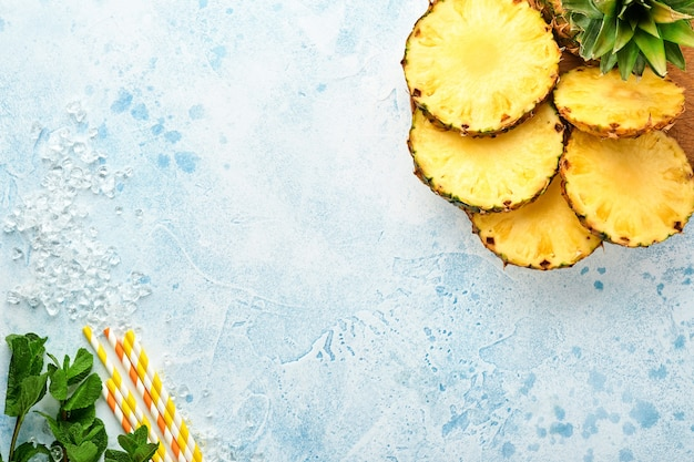 Plasterki dojrzałego ananasa na jasnoniebieskim tle kamienia. owoce tropikalne. widok z góry. wolne miejsce na tekst.
