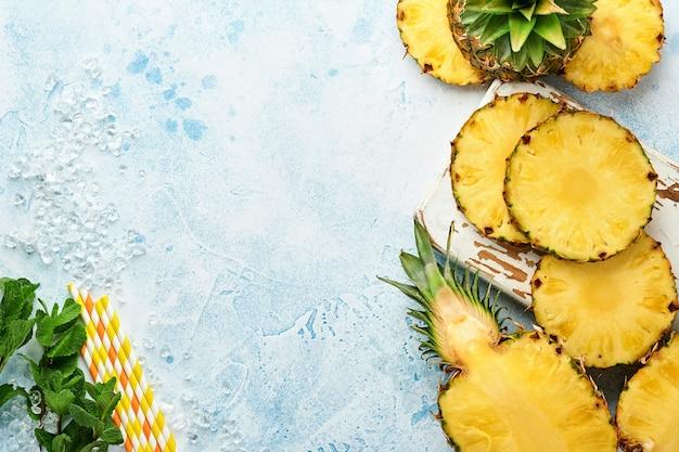 Plasterki dojrzałego ananasa na jasnoniebieskim tle kamienia. owoce tropikalne.