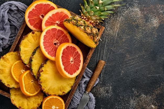 Plasterki dojrzałego ananasa, pomarańczy i grejpfruta w drewnianym pudełku na ciemnym brązowym tle kamienia. owoce tropikalne. widok z góry. wolne miejsce na tekst.