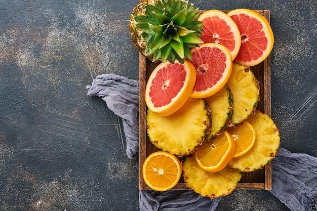 Plasterki dojrzałego ananasa w drewnianym pudełku na ciemnym brązowym tle kamienia. owoce tropikalne. widok z góry. wolne miejsce na tekst. makieta.