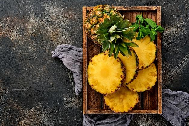 Plasterki dojrzałego ananasa w drewnianym pudełku na ciemnym brązowym tle kamienia. owoce tropikalne. widok z góry. wolne miejsce na tekst.