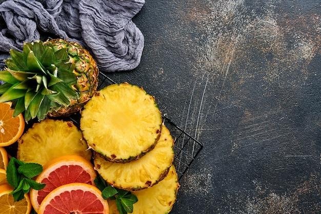Plasterki dojrzałego ananasa w drewnianym pudełku na ciemnym brązowym tle kamienia. owoce tropikalne.