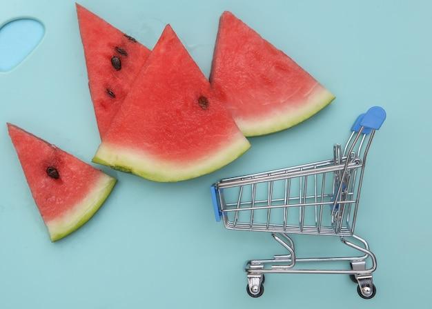 Plasterki dojrzałego arbuza i wózek na zakupy na niebieskim tle. widok z góry