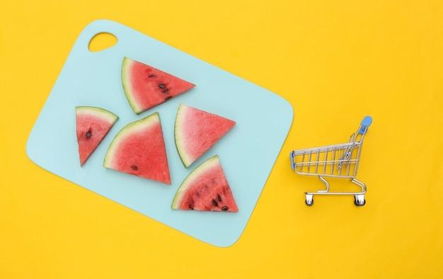 Plasterki dojrzałego arbuza na niebieską deskę i wózek na zakupy. żółte tło. widok z góry