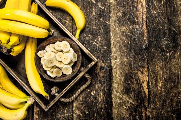 Plasterki dojrzałego banana w misce na drewnianym stole.