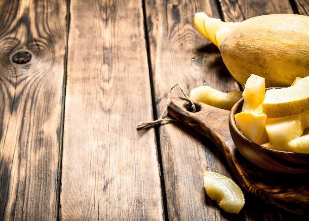 Plasterki dojrzałego melona w drewnianej misce. na drewnianym stole.