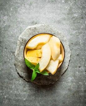 Plasterki dojrzałego melona z gałązkami mięty. na kamiennym tle.