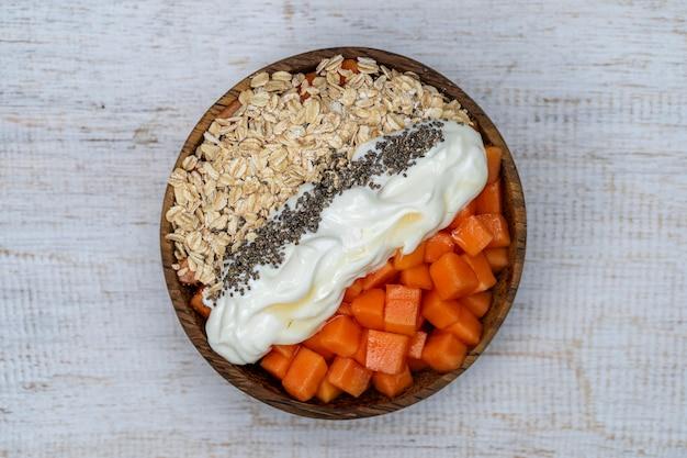 Plasterki dojrzałej słodkiej papai z płatkami owsianymi, nasionami chia i białym jogurtem na misce z orzecha kokosowego