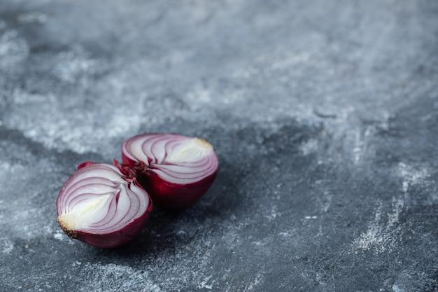 Plasterki fioletowej cebuli na marmurowym tle.