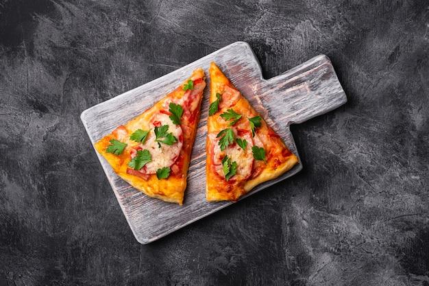 Plasterki gorącej pizzy z serem mozzarella, szynką, pomidorem i natką pietruszki na drewnianej desce do krojenia, powierzchnia z betonu kamiennego, widok z góry