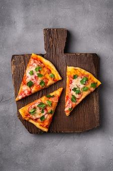 Plasterki gorącej pizzy z serem mozzarella, szynką, pomidorem i pietruszką na brązowej drewnianej desce do krojenia, kamienna deska betonowa, widok z góry