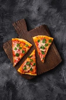 Plasterki gorącej pizzy z serem mozzarella, szynką, pomidorem i pietruszką na brązowej drewnianej desce do krojenia, kamienny betonowy stół, widok z góry