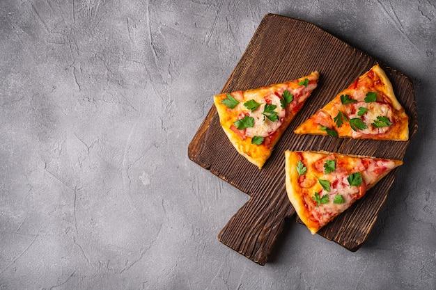 Plasterki gorącej pizzy z serem mozzarella, szynką, pomidorem i pietruszką na brązowej drewnianej desce do krojenia