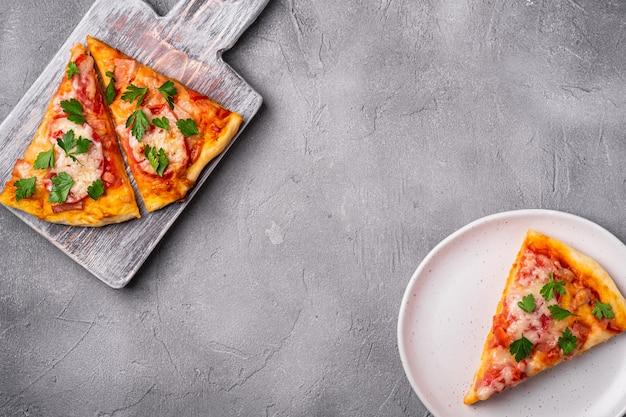 Plasterki gorącej pizzy z serem mozzarella, szynką, pomidorem i pietruszką na drewnianej desce do krojenia i talerzu, kamienna powierzchnia betonowa, widok z góry miejsce na tekst