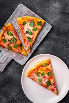 Plasterki gorącej pizzy z serem mozzarella, szynką, pomidorem i pietruszką na drewnianej desce do krojenia i talerzu, kamienny betonowy stół, widok z góry