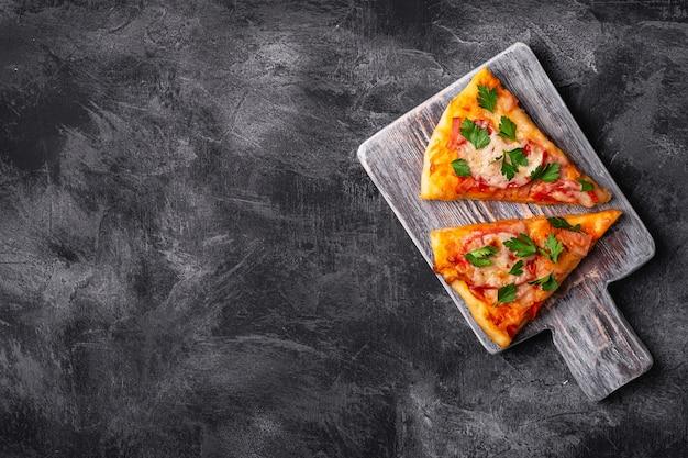 Plasterki gorącej pizzy z serem mozzarella, szynką, pomidorem i pietruszką na drewnianej desce do krojenia