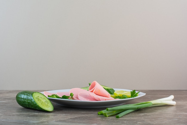 Plasterki gotowanej kiełbasy, pietruszki, ogórka i zielonej cebuli na talerzu, na marmurowym tle.