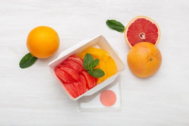 Plasterki grejpfruta i pomarańczy z widoku z góry znajdują się w pudełku na lunch na stole obok połowy grejpfruta i dwóch pomarańczy. przekąska owocowa w koncepcji pracy.
